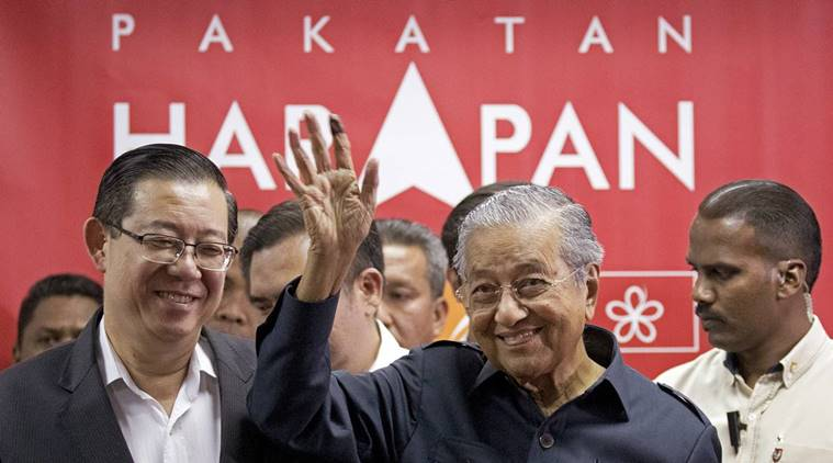Malaysia's Prime Minister Mahathir Mohamad, center, waves next to newly appointed Finance Minister Lim Guan Eng, left, after a press conference to announce his cabinet members in Petaling Jaya, Malaysia, Saturday, May 12, 2018. Mahathir has appointed the ethnic Chinese as finance minister, the first ethnic minority to hold the powerful post in 44 years. (AP Photo/Andy Wong)